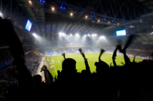 Silhouettes of fans celebrating a goal on football / soccer match
